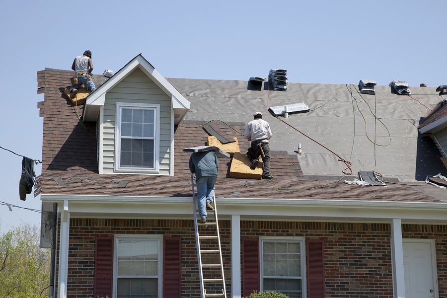 Roofers replacing damaged shingles after storm with very high winds came through over night